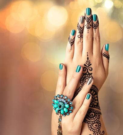 manicura: Mehndi tatuaje. Manos de mujer con negro tatuaje de henna