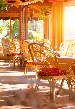 sunny season: Restaurant interior. Summer coffee terrace with tables and wicker chairs