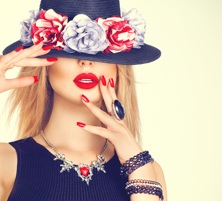 uroda: Beautiful sexy kobieta z czerwonymi ustami i manicure w nowoczesnym czarnym kapeluszu Zdjęcie Seryjne