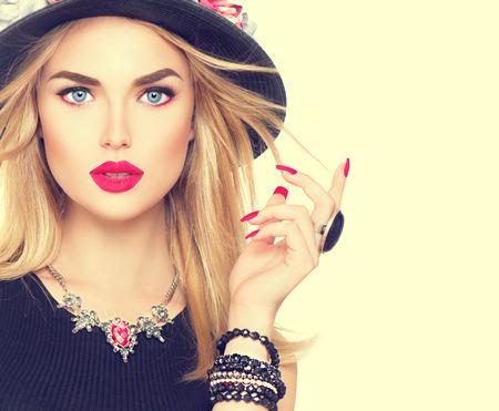 modelo: Hermosa mujer rubia sexy con labios rojos y manicura en el sombrero negro moderno