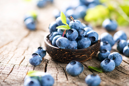 Juicy and fresh blueberries with green leaves in wooden bowl Stockfoto