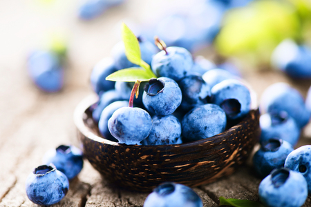 wildberry: Blueberries in wooden bowl over rustic wooden table closeup