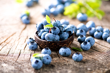 Juicy and fresh blueberries with green leaves in wooden bowl Imagens