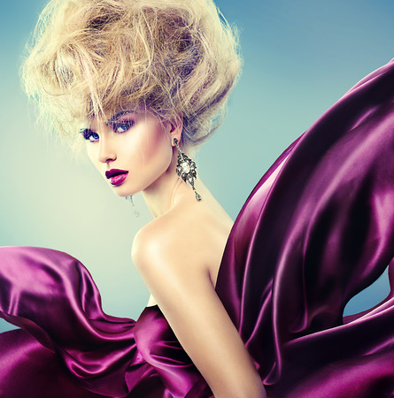 moda: Donna di fascino con updo acconciatura e trucco luminoso vestito di seta viola da volo