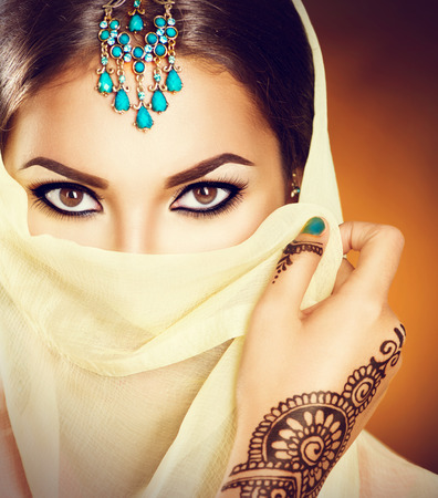 mehendi: Beautiful indian woman with traditional turquoise jewels hiding her face
