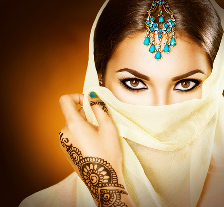 sari: Beautiful indian woman with traditional turquoise jewels hiding her face