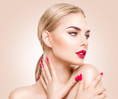 rubia: Hermosa mujer modelo con maquillaje perfecto, labios rojos y uñas