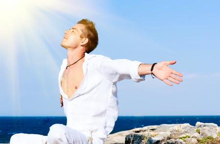 Apuesto joven sentado al aire libre cerca del mar con los brazos abiertos Foto de archivo