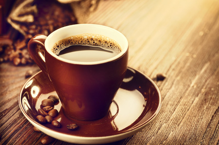 Cup of aromatic coffee over wooden table. Coffee beans Imagens