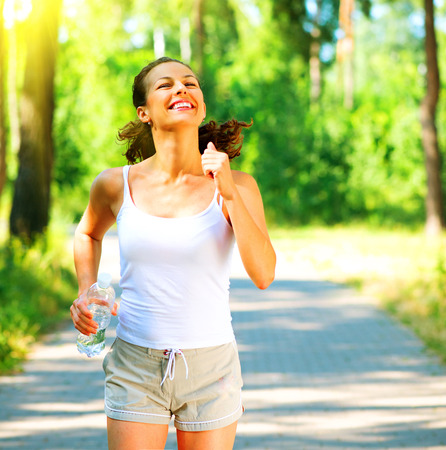 Girl running with bottle of water. Young sporty woman jogging outdoor Stock Photo