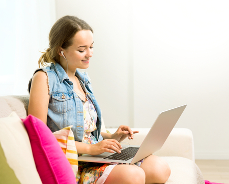 Schoonheid tiener meisje zittend op de bank thuis en met behulp van laptop Stockfoto