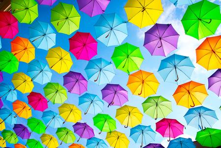 푸른 하늘 위에 여러 가지 빛깔의 우산 매달려. 추상적 인 배경
