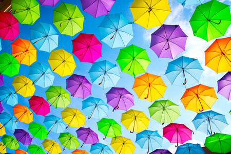 Hanging multicolored umbrellas over blue sky. Abstract background