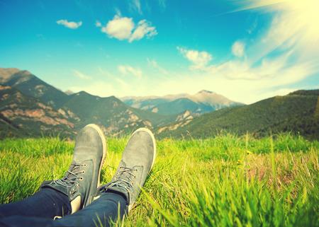 ハイカーは自然の眺めを楽しんでします。草原と山々 写真素材