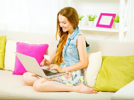 learning online: Beauty teenage girl sitting on sofa, using laptop