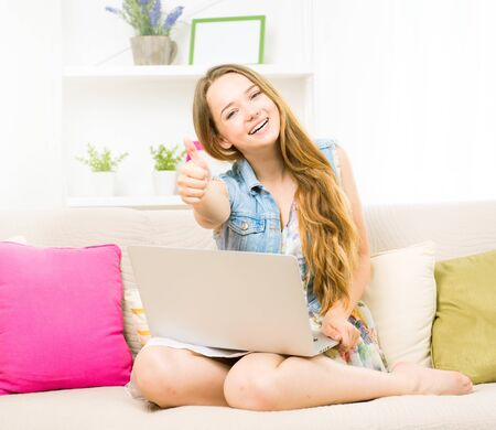 thumbup: Beauty teenage girl sitting on sofa, using laptop and smiling. Showing thumbs up