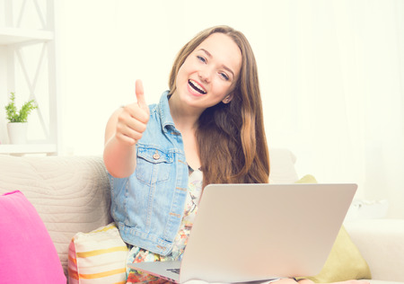 thumbup: Pretty teenage girl sitting on sofa at home with her laptop, making thumb up