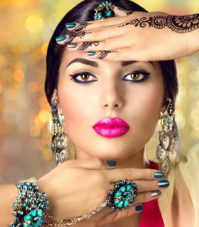 moda: Piękna indyjska portret kobiety. Hinduska dziewczynka z orientalnych akcesoriów - kolczyki, bransoletki i pierścionki Zdjęcie Seryjne