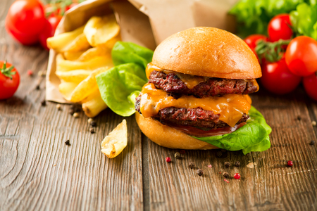 junk: Hamburger with fries on wooden table