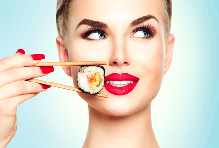 red food: Beautiful blonde girl with red lips and manicure eating sushi rolls Stock Photo