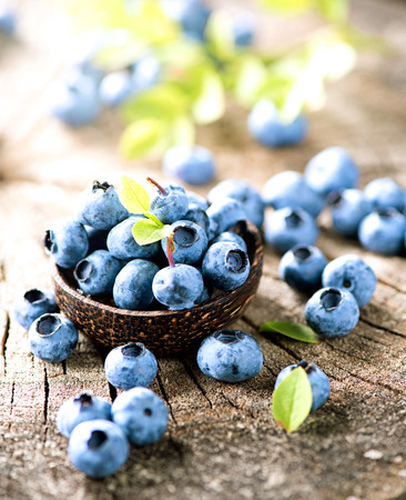 Blueberries in wooden bowl over rustic wooden table closeup