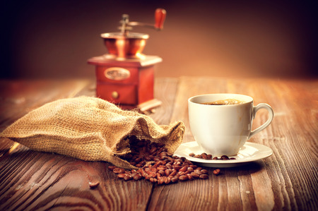 frijoles: Taza de café con el saco lleno de granos de café tostado y molino de café en la mesa de madera