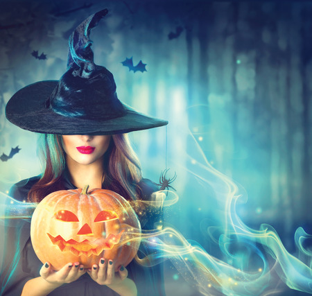magic hat: Halloween witch with a magic pumpkin in a dark forest Stock Photo