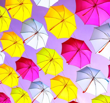 vivid: Colorful umbrellas urban street decoration. Hanging Multicolored umbrellas over blue sky Stock Photo