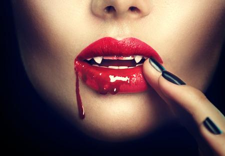 時尚: 萬聖節。性感的吸血鬼婦女的嘴唇有血