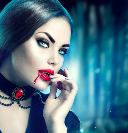 Halloween vampire. Beauty sexy vampire girl with blood on her mouth 스톡 콘텐츠