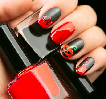manicura: El diseño del arte del clavo de Halloween. Nailpolish mate negro con gotas de sangre y la calabaza