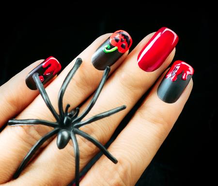 nails: Halloween Nail art design. Black matte polish with blood drips and pumpkin Stock Photo