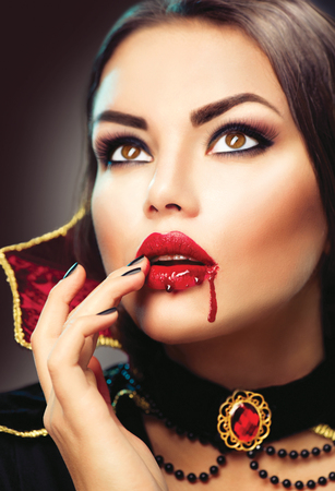 Halloween vampire woman portrait. Beauty sexy vampire lady with blood on her mouth