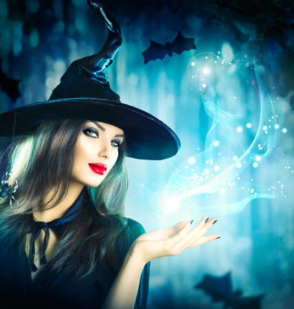 magic hat: Halloween Witch holding magical light in her hand Stock Photo