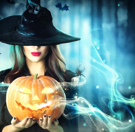 calabazas de halloween: Bruja de Halloween con una calabaza mágica en un bosque oscuro
