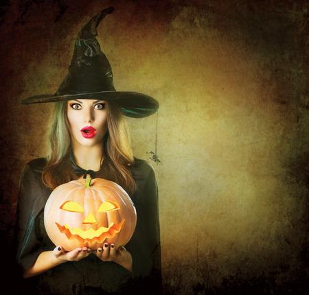 sorprendido: La bruja de Halloween sosteniendo tallada Jack linterna de calabaza Foto de archivo