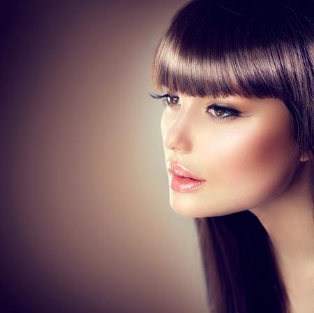 Mujer de la belleza con maquillaje hermoso y pelo castaño liso sano