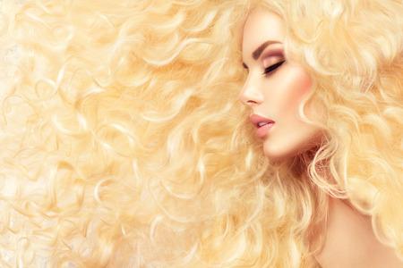 건강한 긴 물결 모양의 머리를 가진 패션 금발 소녀