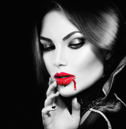 young woman face: Beauty sexy vampire girl with dripping blood on her mouth Stock Photo