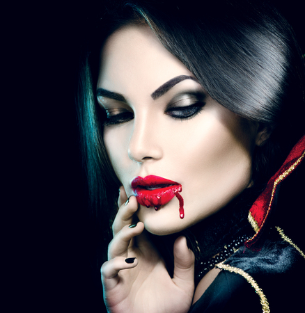 fangs: Beauty sexy vampire girl with dripping blood on her mouth Stock Photo