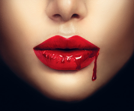 horror: Sexy vampire woman lips with dripping blood