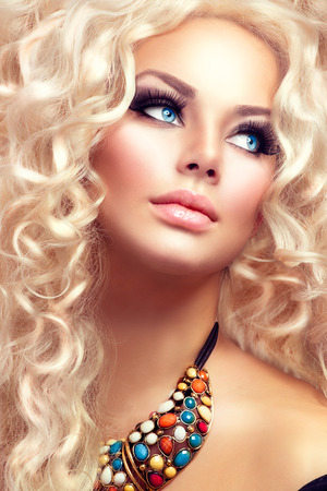 perming: Beauty girl with healthy long curly hair. Blonde woman portrait
