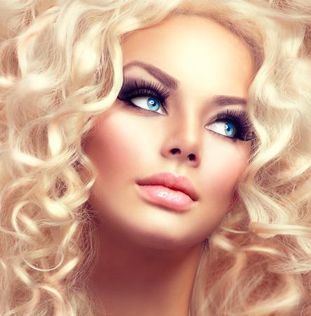 rubia ojos azules: Muchacha de la belleza con el pelo rizado largo sano Foto de archivo