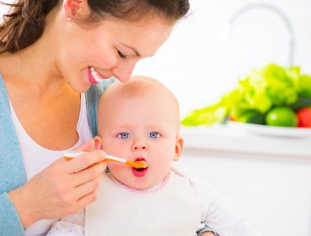 trẻ sơ sinh: Mẹ nuôi bé gái cô với một muỗng. Thức ăn trẻ em