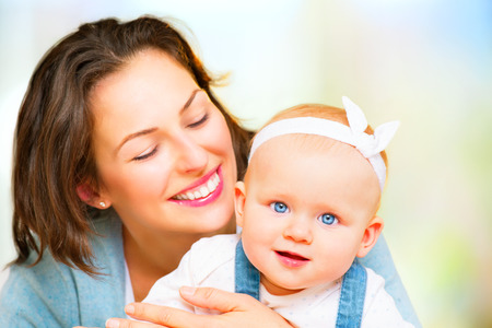 love hug: Happy family. Mom and baby girl kissing and hugging at home Stock Photo