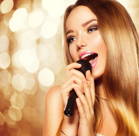 Singing teenage girl with microphone over golden glowing background. Karaoke party