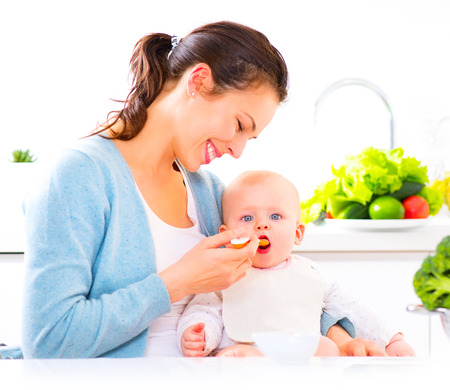 Mother feeding her baby girl with a spoon. Baby food Stockfoto