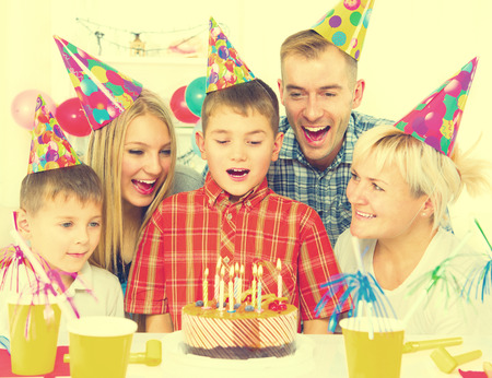 blows: Birthday. Little boy blows out candles on birthday cake at party