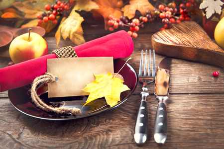 dinner party: Thanksgiving dinner wooden table served, decorated with bright autumn leaves Stock Photo