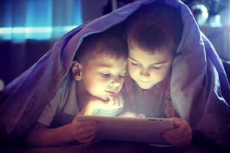 Geceleri battaniyenin altında tablet pc kullanarak İki çocuk Stok Fotoğraf